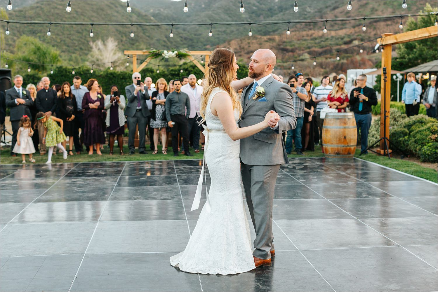 Family and friends watch as bride and groom share their first dance as husband and wife - https://brittneyhannonphotography.com